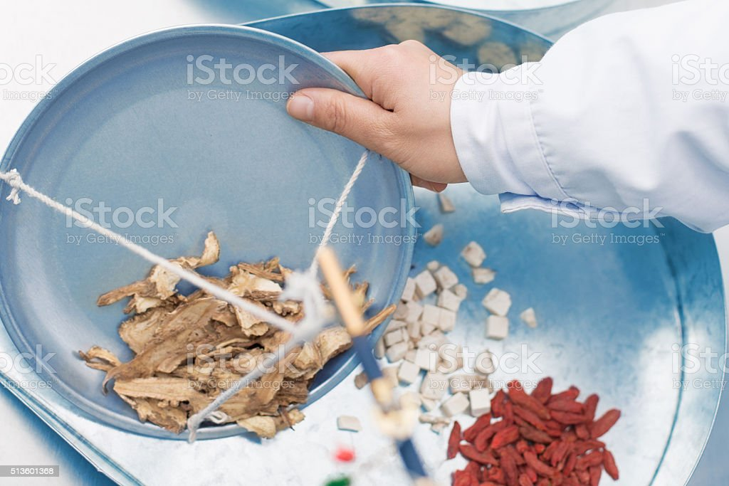 Doctor Weighing Herbal Medicine with Scale stock photo