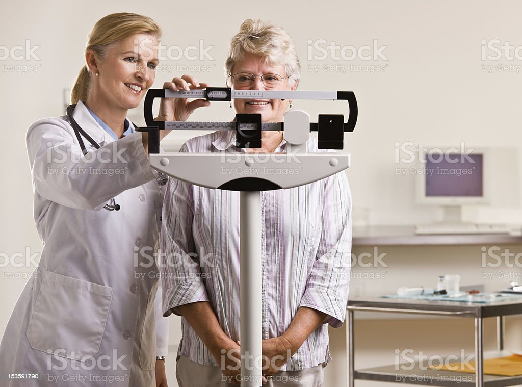 Doctor weighing senior woman stock photo