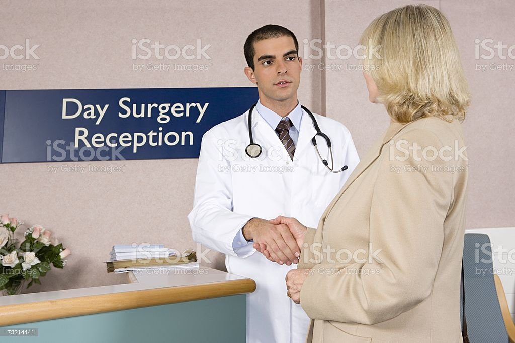 Doctor welcoming patient stock photo