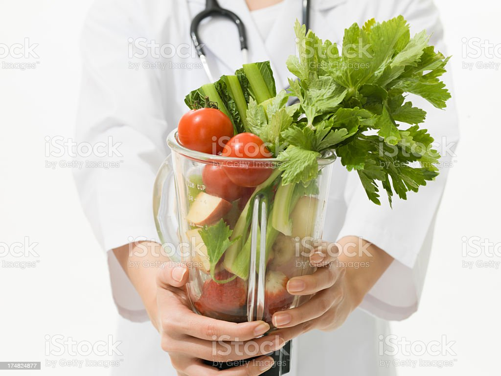 Doctor who presents the vegetables included in a juicer royalty-free stock photo