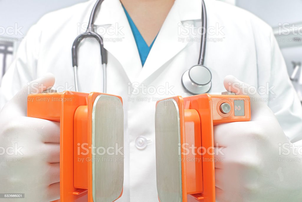 doctor with a defibrillator electrodes stock photo