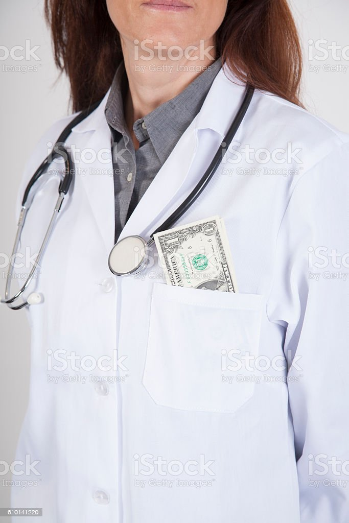 doctor with a wad of dollars in her pocket stock photo