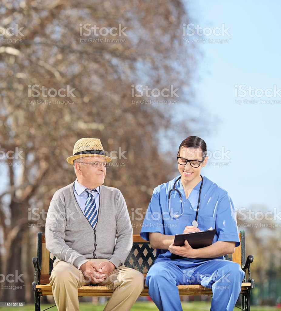 Doctor with clipboard and senior sitting in park stock photo