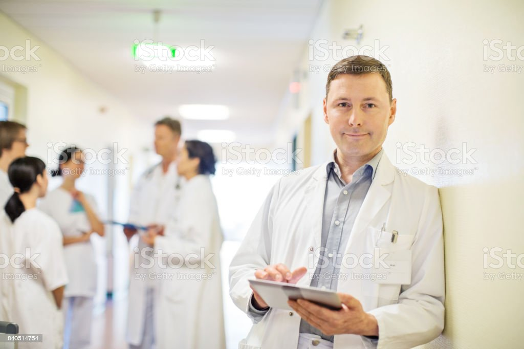 Relaxed male doctor holding digital tablet standing in hospital...