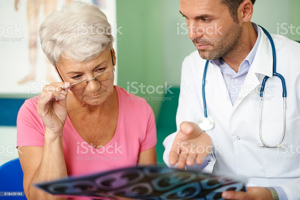 Doctor with his senior patient analyzing medical test stock photo