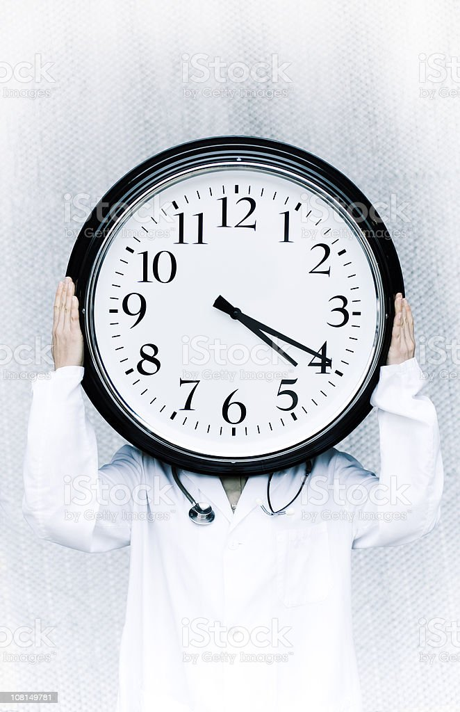 Doctor with Lab Coat and Stethoscope Holding Up Giant Clock stock photo