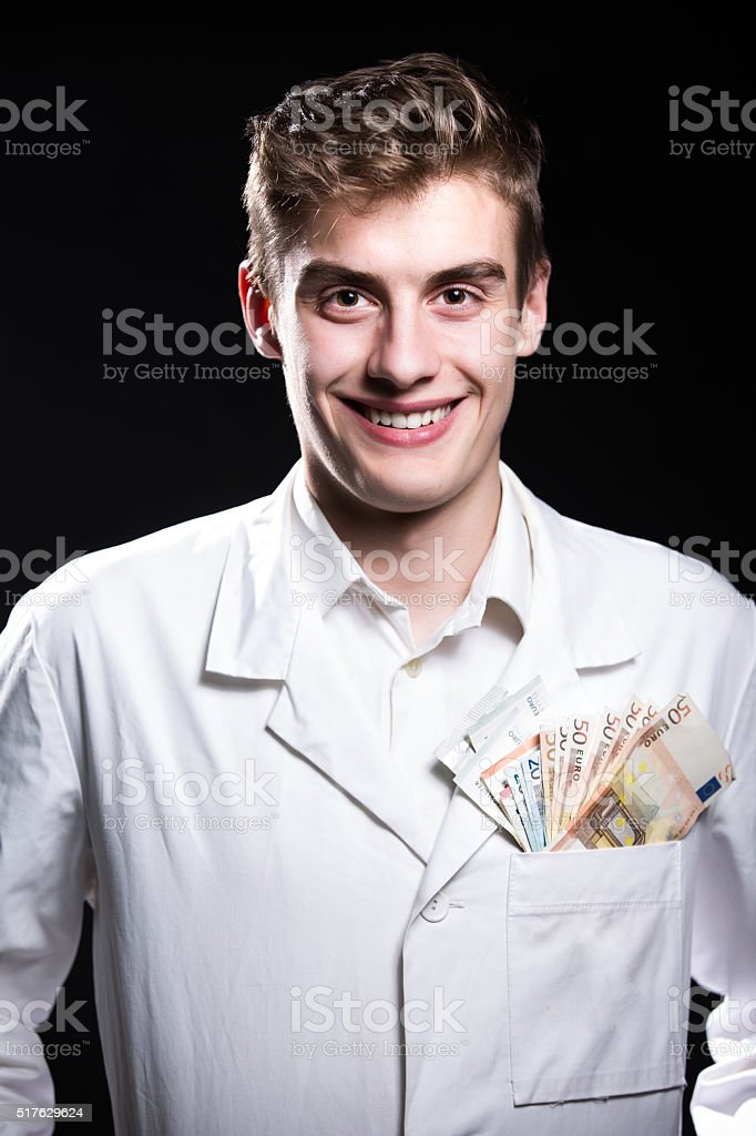 Doctor with money in pocket.Corruption in Health Industry.Rich doctor stock photo