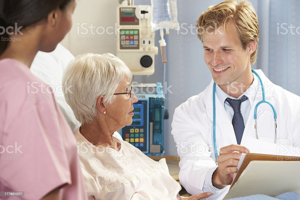 Doctor With Nurse Talking To Senior Female Patient In Bed royalty-free stock photo