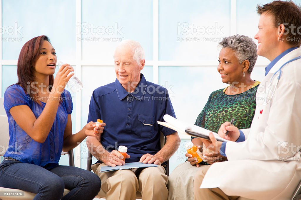 Doctor with patients discussing prescription medication abuse. stock photo