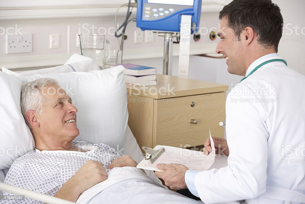Doctor with senior male patient on USA Hospital ward stock photo
