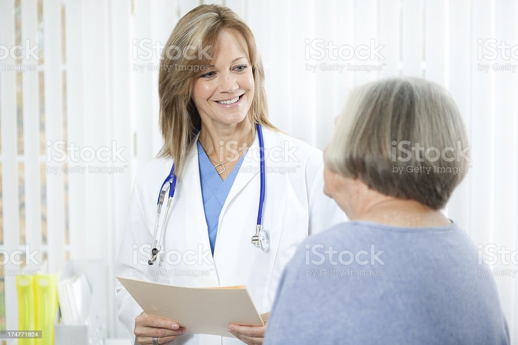 Doctor with Senior Woman Patient in Medical Clinic Office Hz royalty-free stock photo