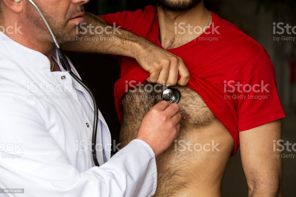 doctor with stethoscope listening to patients heartbeat stock photo