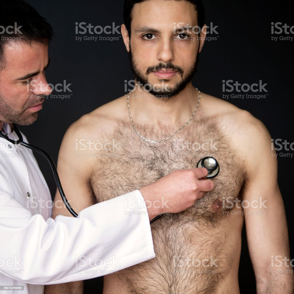 doctor with stethoscope listening to shirtless patients heartbeat stock photo