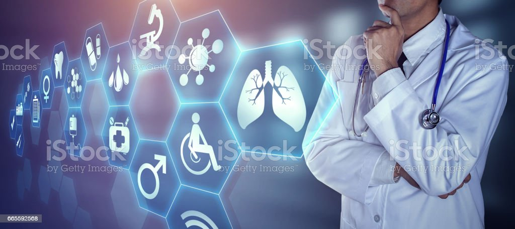 Doctor with stethoscope touching the digital icons stock photo