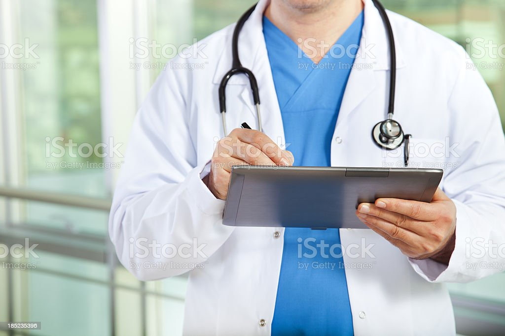 Doctor with stethoscope writing on tablet device royalty-free stock photo