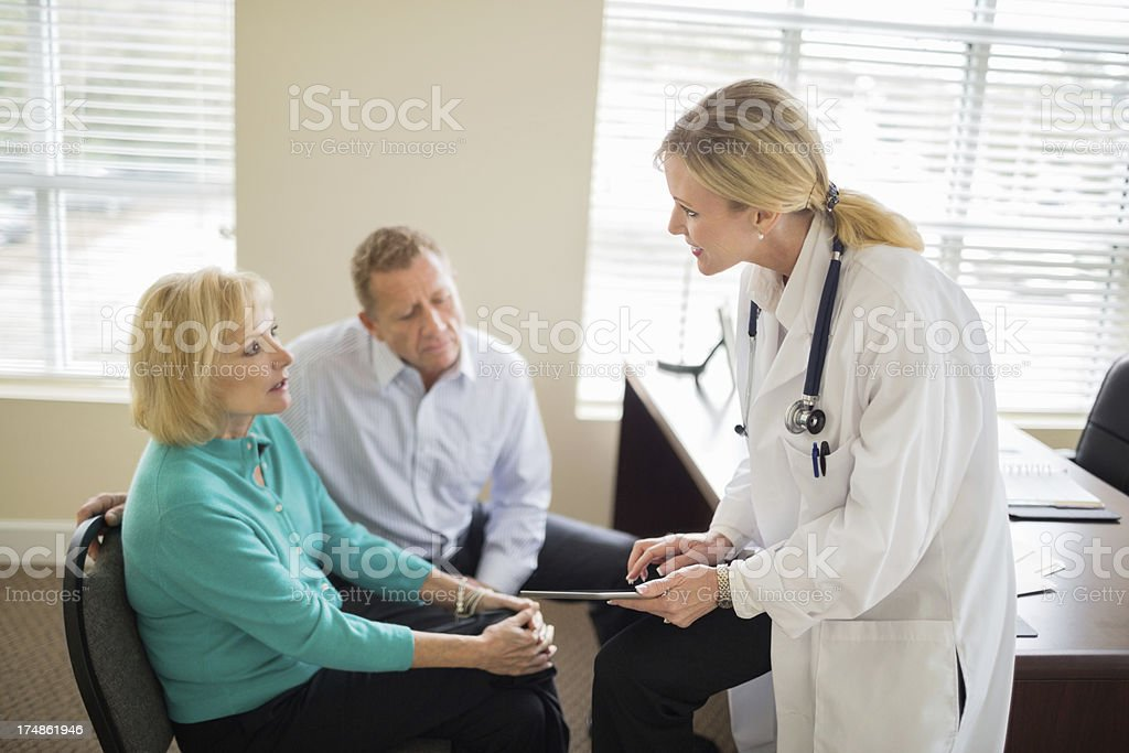 Female doctor with digital tablet explaining medical exam results to...