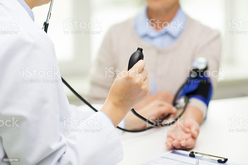 doctor with tonometer and senior woman at hospital stock photo