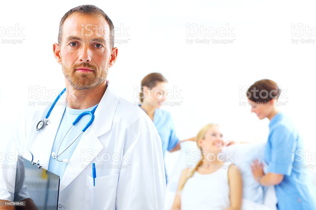 Doctor with two nurses and a patient in the background royalty-free stock photo