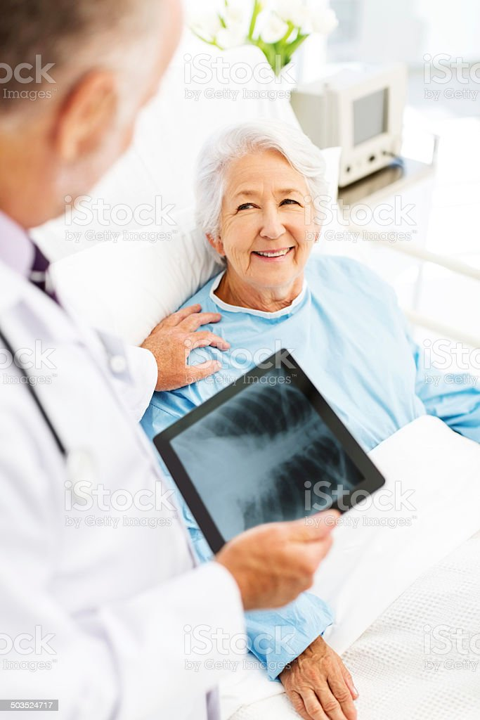 Doctor With X-Ray On Digital Tablet Consoling Patient In Hospital stock photo