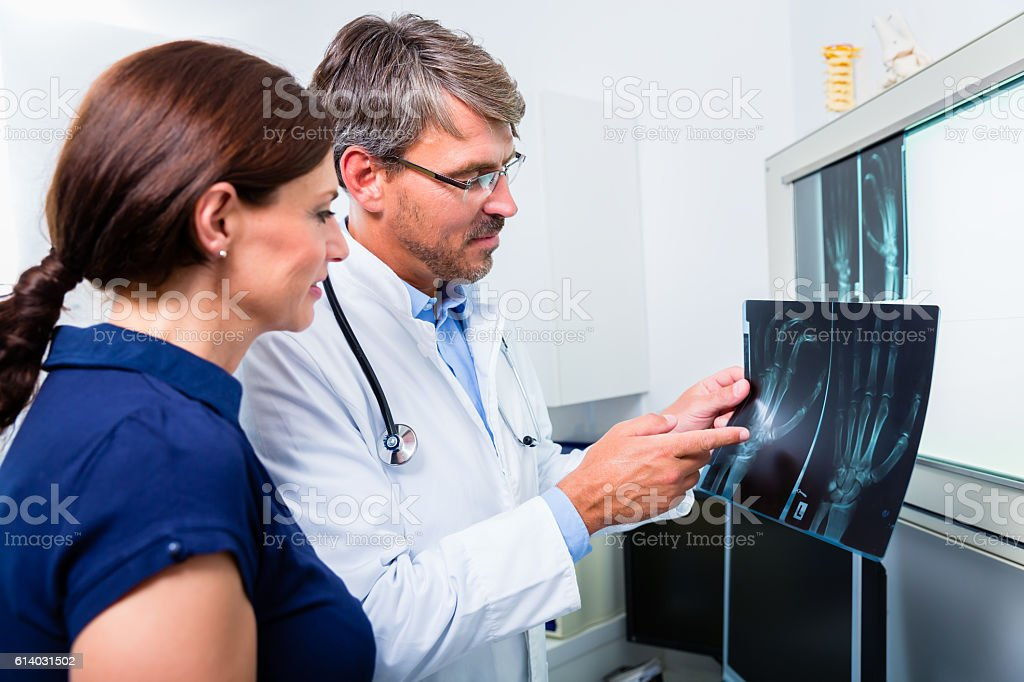 Doctor with x-ray picture of patient hand stock photo