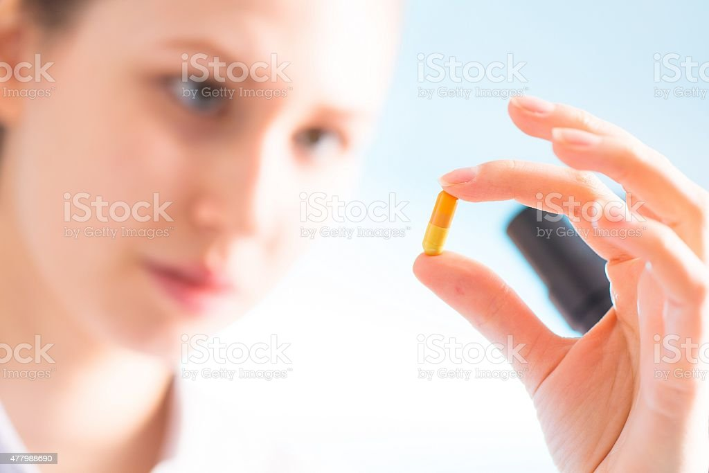 Doctor woman hold medicine capsule, pill in hand stock photo