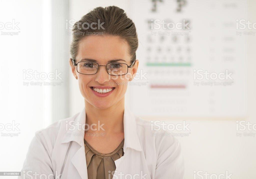Doctor woman in eyeglasses near snellen chart stock photo