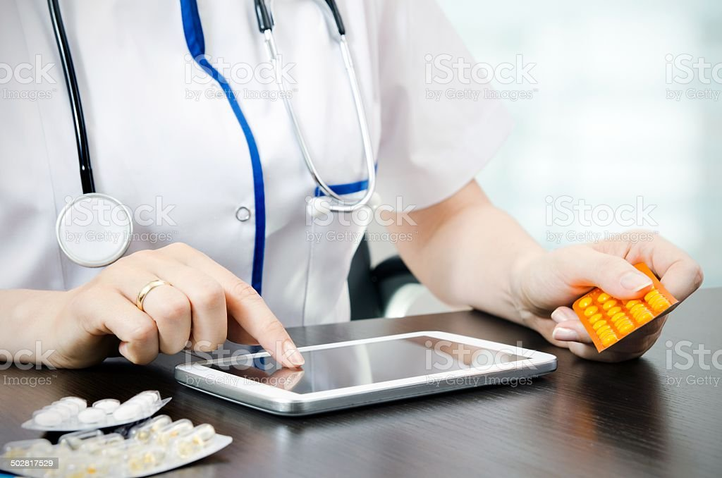 Doctor working on a digital tablet stock photo