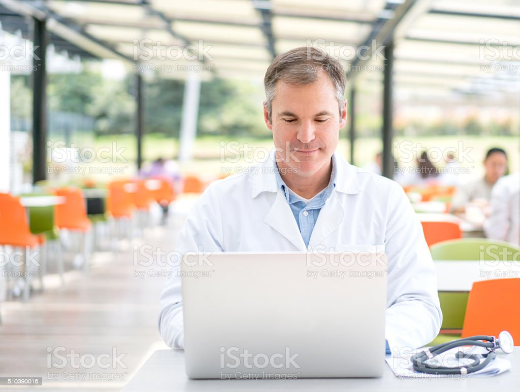 Doctor working on a laptop at the cafeteria stock photo