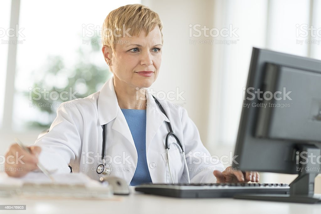 Doctor Working On Computer At Desk stock photo
