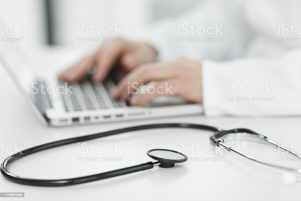 Doctor working on laptop stock photo