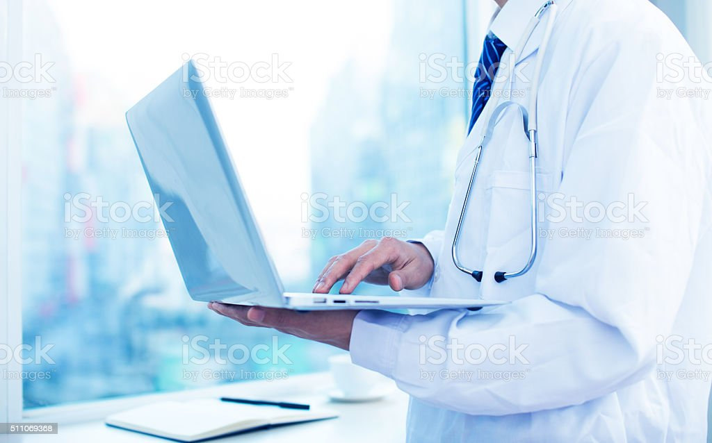 Doctor working with laptop stock photo