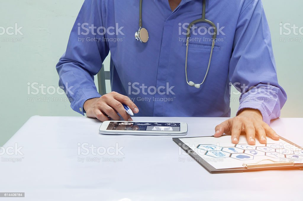 Doctor working with tablet at desk stock photo