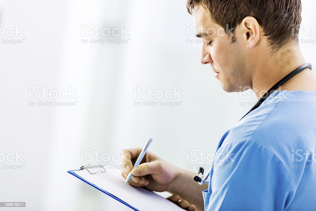 Doctor writing a medical chart. stock photo