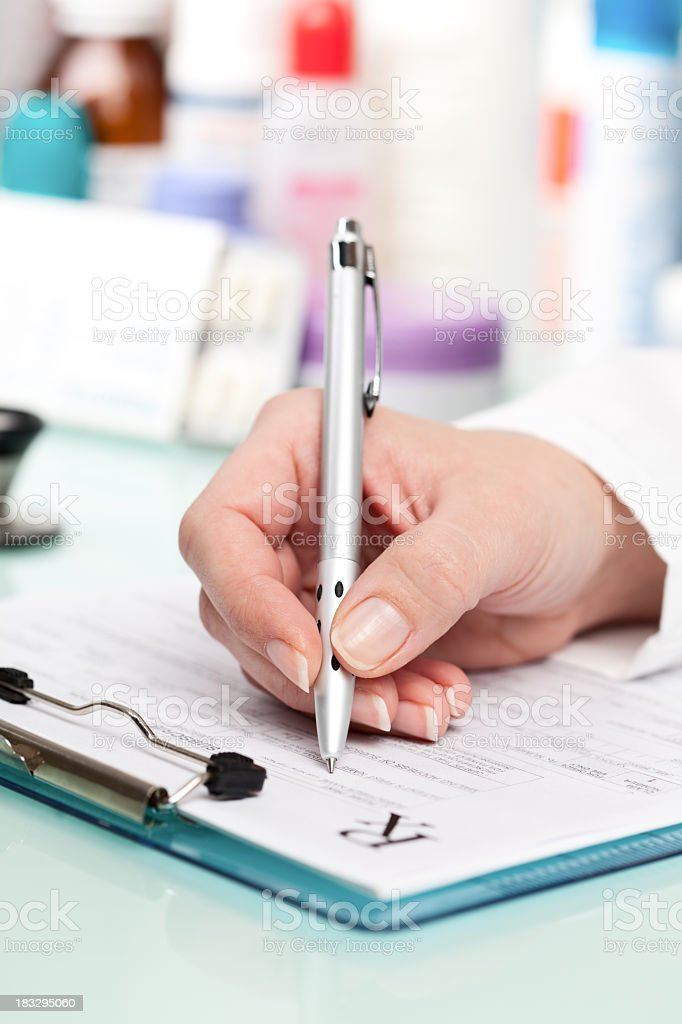 Doctor writing a prescription on medical exam stock photo
