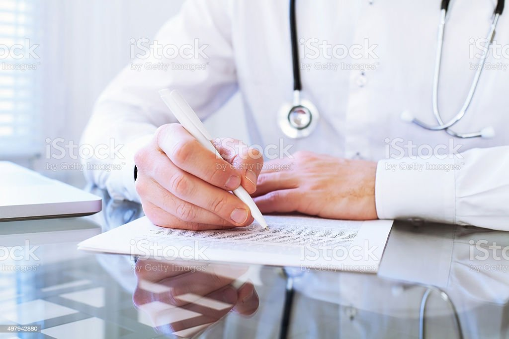 doctor writing diagnosis stock photo