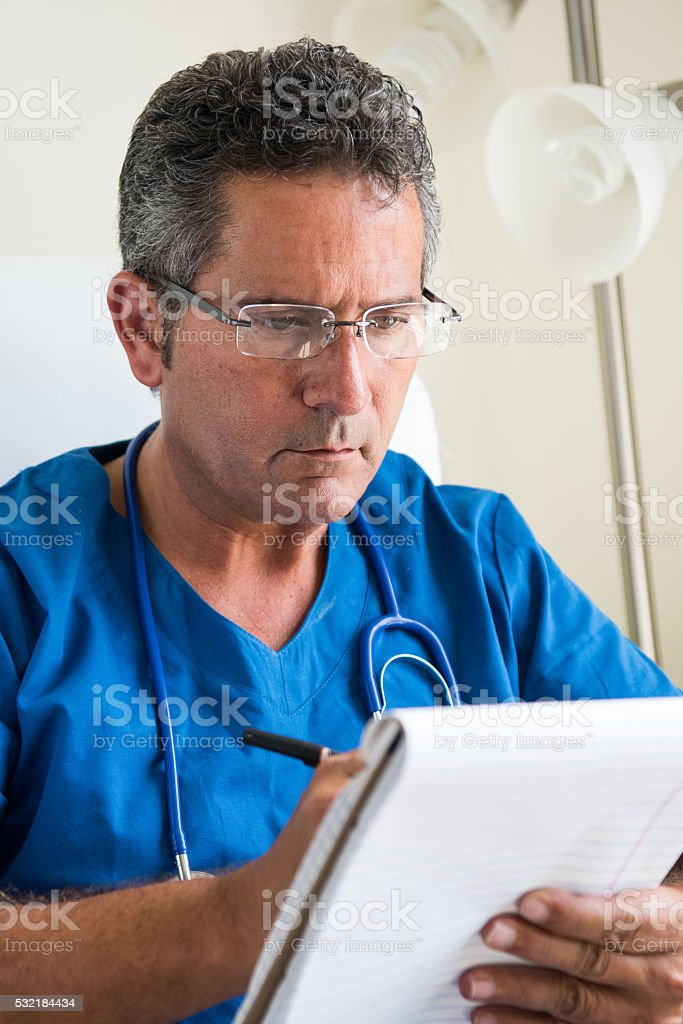 Doctor writing in a notebook stock photo