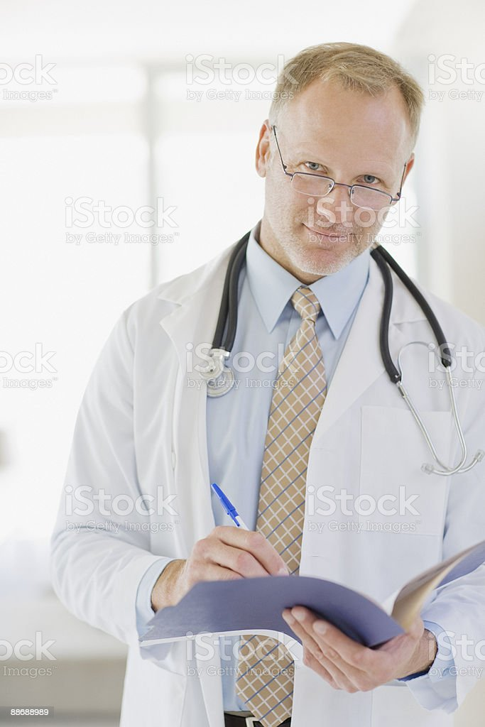 Doctor writing in medical record royalty-free stock photo