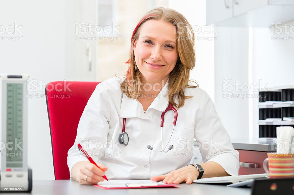 Doctor writing medical prescription in surgery stock photo