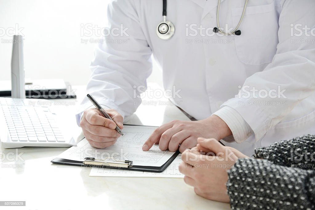 Doctor writing medical record stock photo