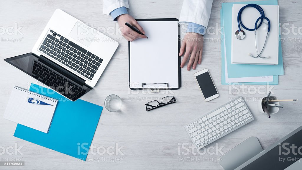 Doctor writing medical records stock photo