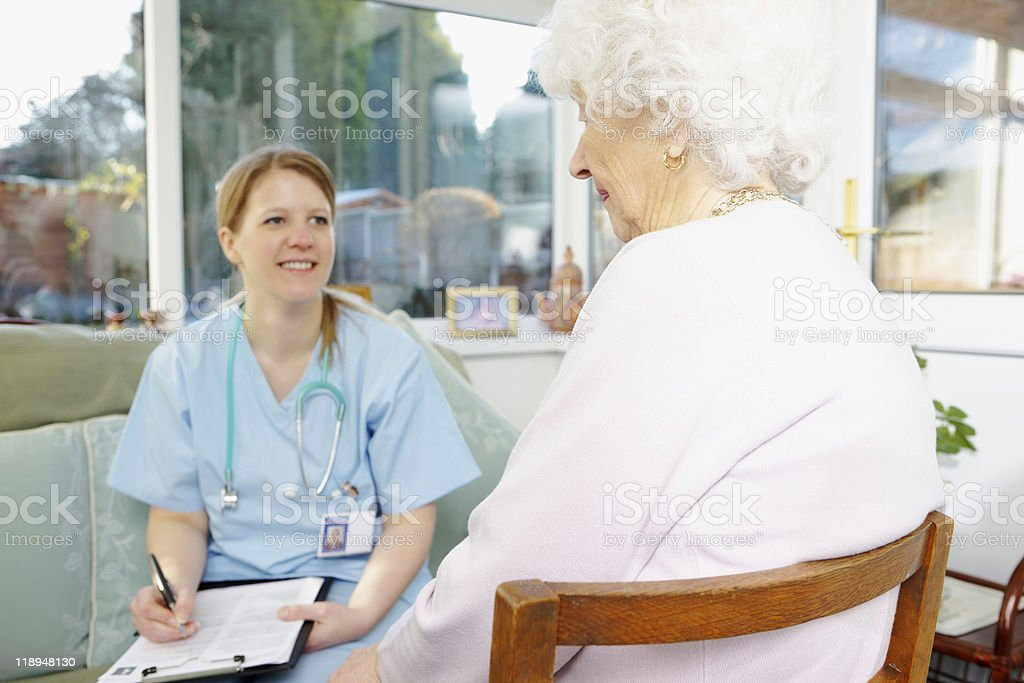 Doctor writing medical report for senior patient in care home royalty-free stock photo