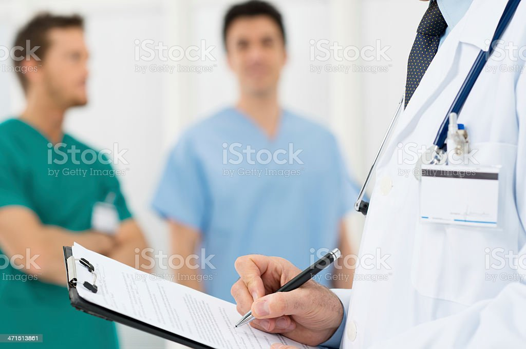 A doctor writing on a clipboard stock photo