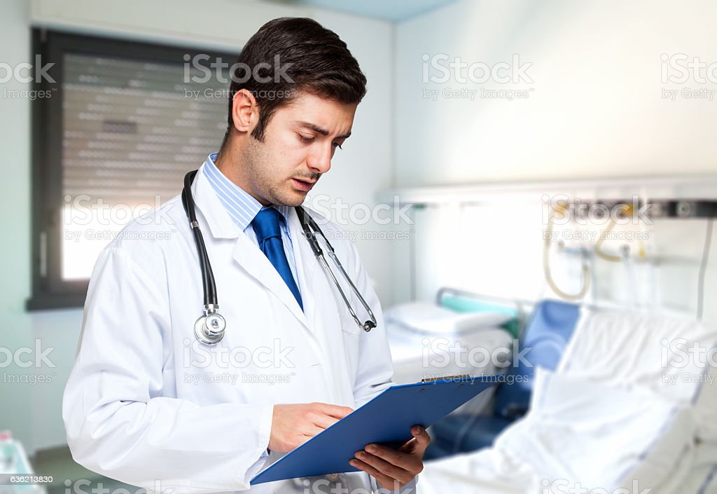 Doctor writing on a clipboard stock photo