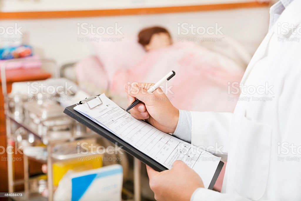 doctor writing on a medical chart with patient stock photo