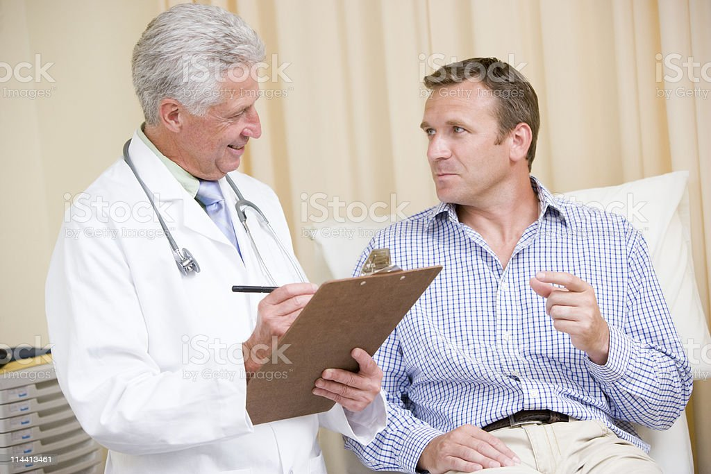 Doctor writing on clipboard while giving man checkup stock photo