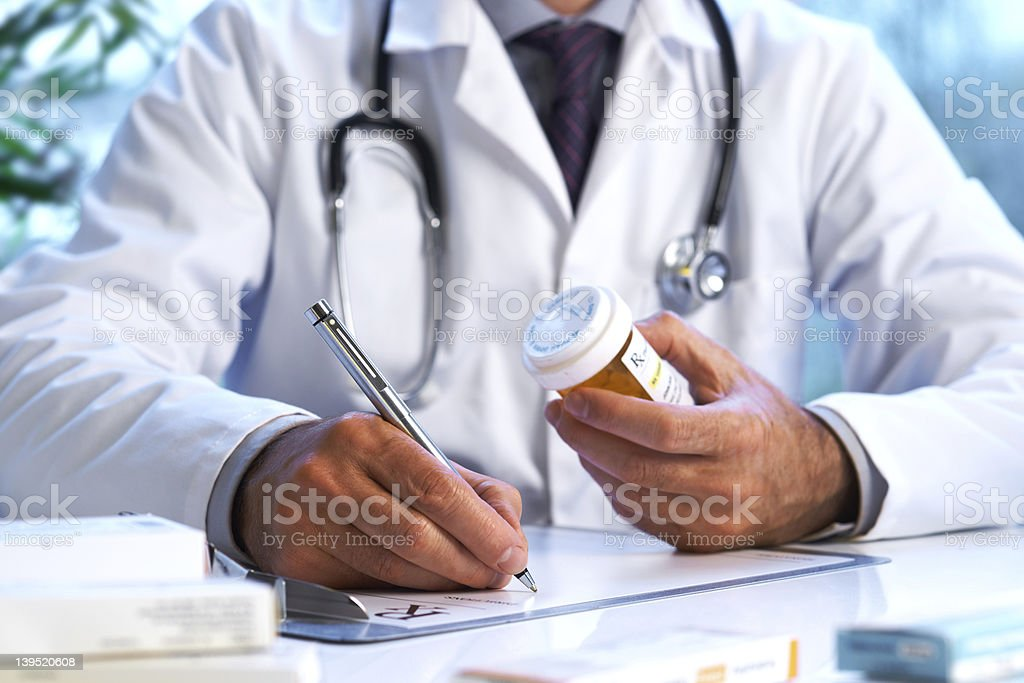 Doctor writing out RX prescription stock photo