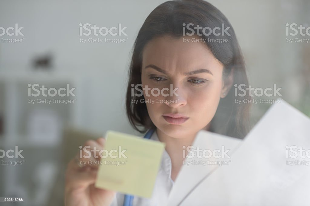 Doctor writing patient test results stock photo