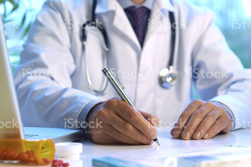 Doctor writing prescription or medical notes royalty-free stock photo