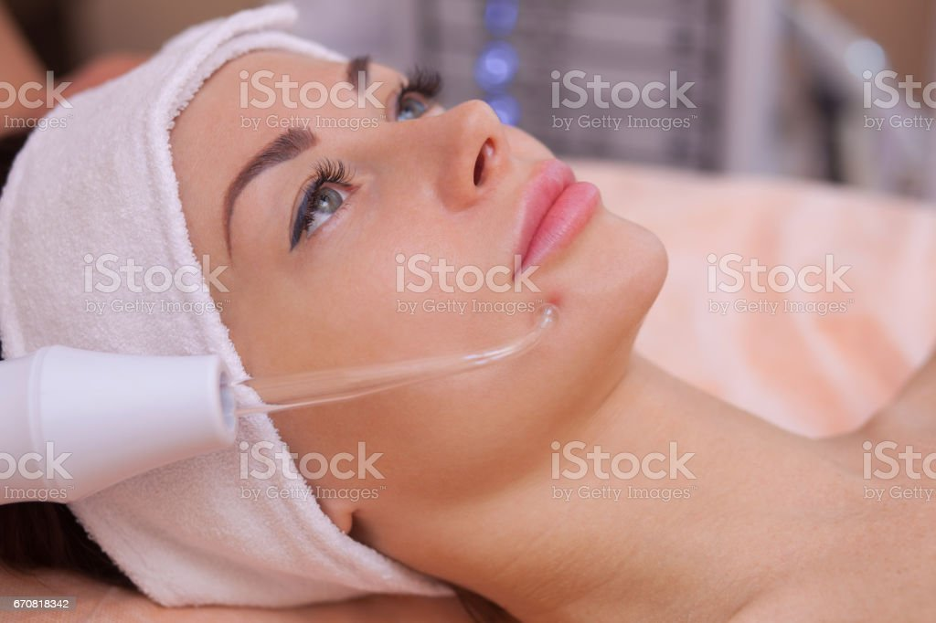 doctor-cosmetologist makes the procedure Microcurrent therapy of the facial skin of a beautiful, young woman stock photo