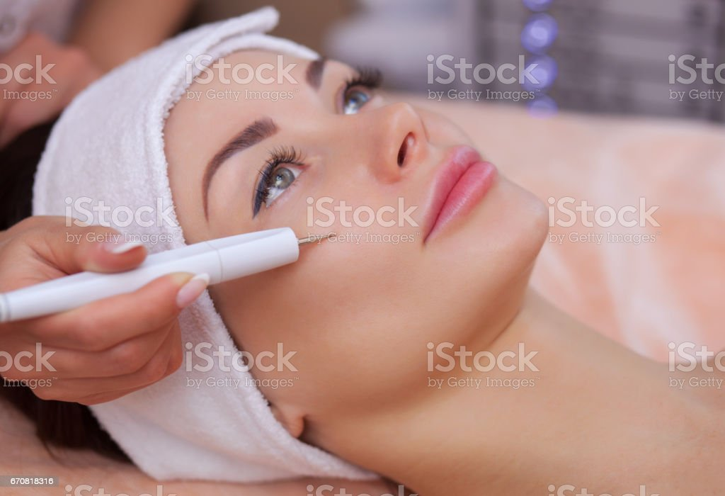 doctor-cosmetologist makes the procedure treatment of Couperose of the facial skin of a beautiful, young woman in a beauty salon stock photo